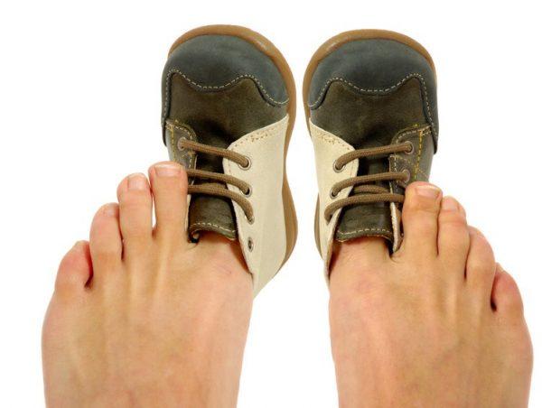 Большие пальцы взрослых ног в детских ботиночках