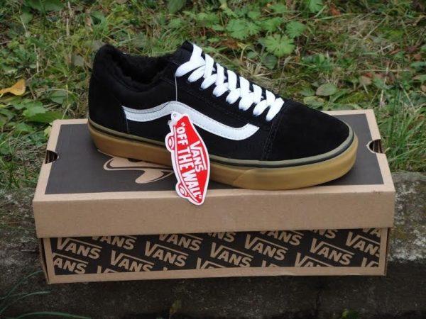 Чёрная кроссовка с биркой стоит на коробке на траве