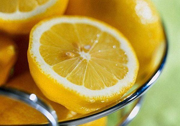 Лимоны в мисочке, на переднем плане половинка лимона