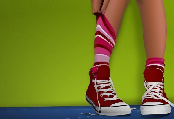 На фоне зелёной стены ноги с полосатых носках и красных кедах