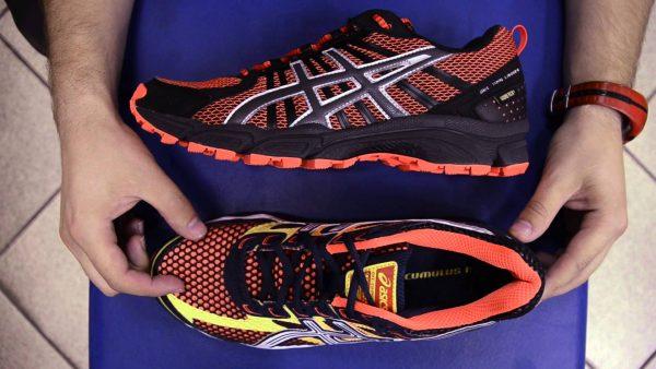 Руки держат оранжево-чёрные кроссовки