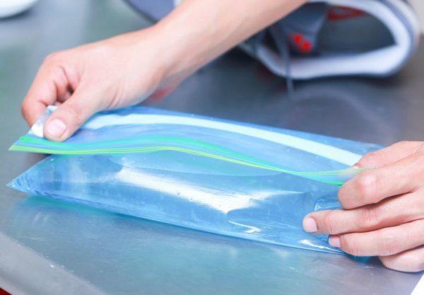 Руки сворачивают голубой пакет с водой