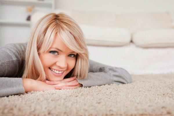 Девушка лежит на чистом ковре