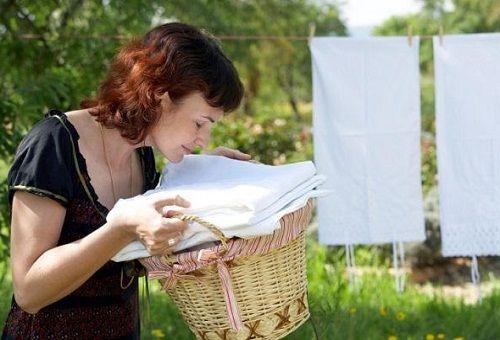 Девушка нюхает бельё в плетёной корзине