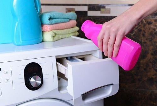 Из розового флакона наливают средство в лоток стиральной машины