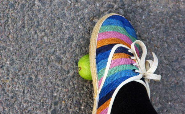 Нога, надавливающая на зелёный орех