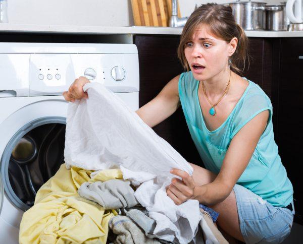 Женщина рассматривает бельё перед стиркой в машинке