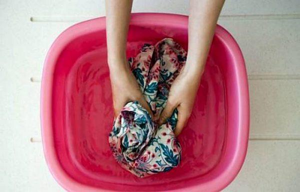 Руками стирают в розовом тазике