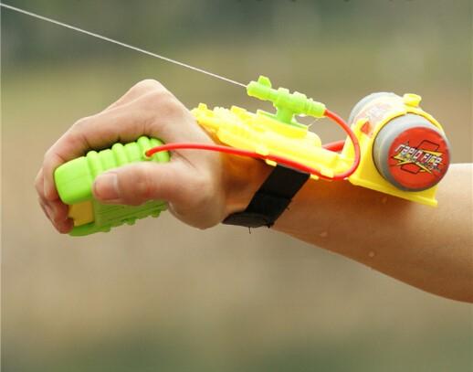 В руке жёлтый водяной пистолет