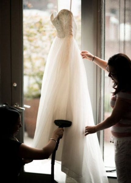 Женщины, отпаривающие свадебное платье отпаривателем