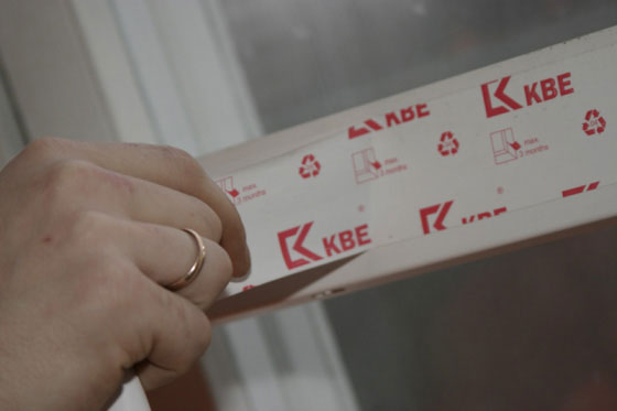 Процесс снятия защитной плёнки с пластикового окна
