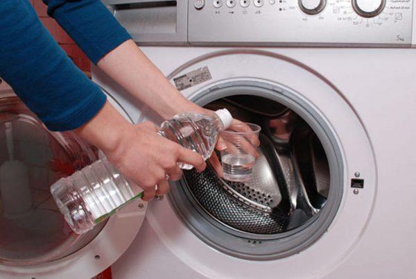 Наливают уксус в стакан для очистки барабана стиральной машины
