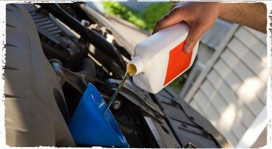 Через воронку заливают машинное масло