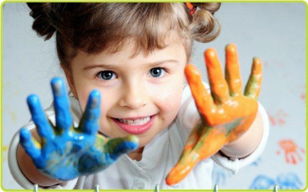 Девочка показывает руки в голубой оранжевой краске