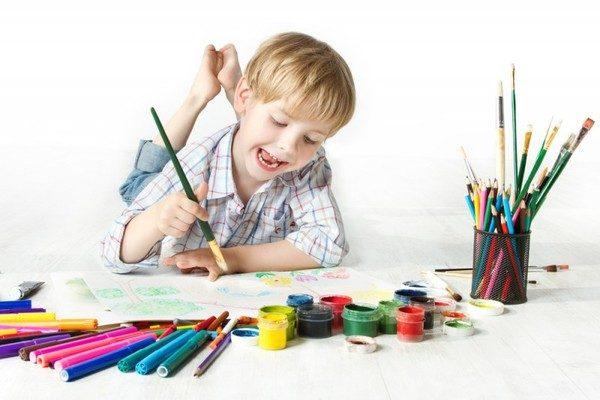 Мальчик лежит на животе и рисует красками