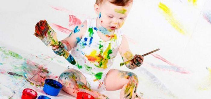 Мальчик разрисовывает себя гуашью