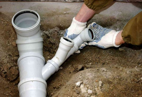 Пластиковая канализационная труба в руках
