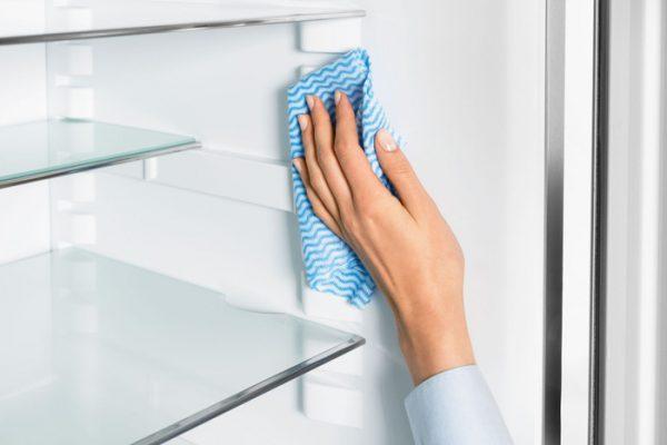 Женщина моет стенки холодильника