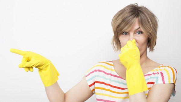 Женщина в перчатках закрывает рукой нос