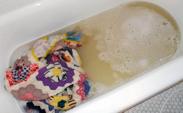 Цветастое одеяло в ванне с грязной водой
