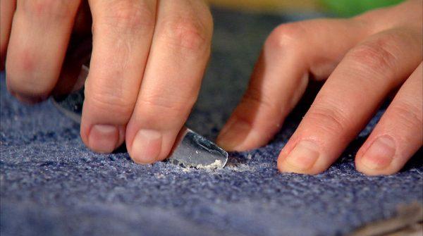 С синей ткани ножом счищают воск