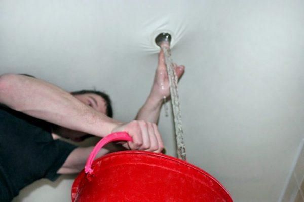 Сливают воду через отверстие в натяжном потолке в ведро