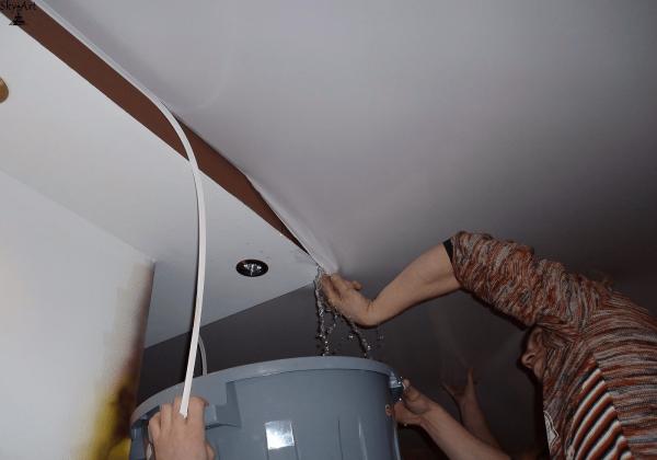 Сливают воду с натяжного потолка