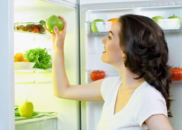 Женщина ставит яблоко в холодильник