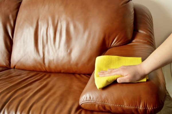 Вытирают кожаный диван жёлтой тряпкой