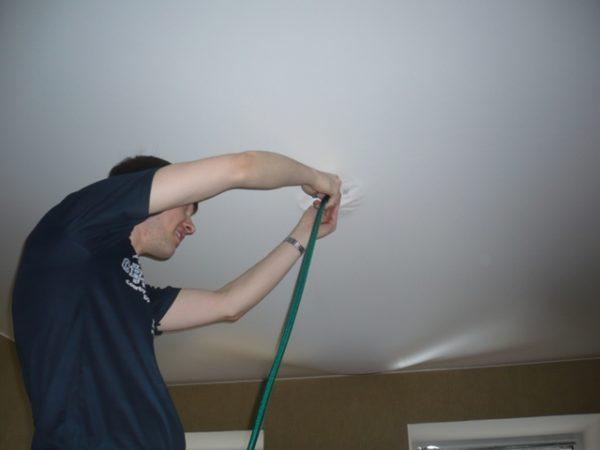 Вставляют шланг в отверстие в натяжном потолке