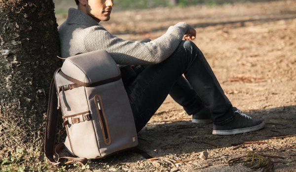 Парень сидит около дерева, рядом серый рюкзак