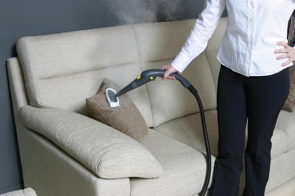 Девушка парогенератором чистит диван