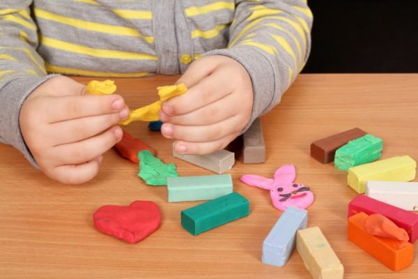 Жёлтый пластилин в руках ребёнка