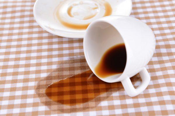 Перевёрнутая чашка, блюдце и пятно от кофе на скатерти