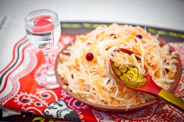 Соленая капуста с брусникой в хохломской посуде, ложка и рюмка водки