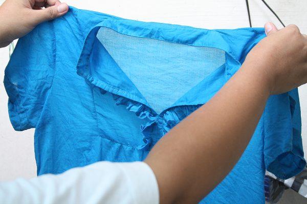 Держат в руках голубую блузу