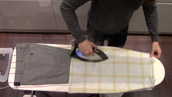 Утюгом гладят брюки через салфетку