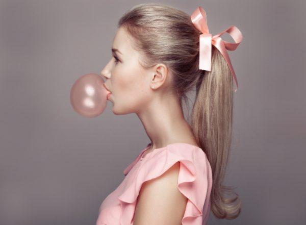 Блондинка с розовым бантом выдувает пузырь из жвачки