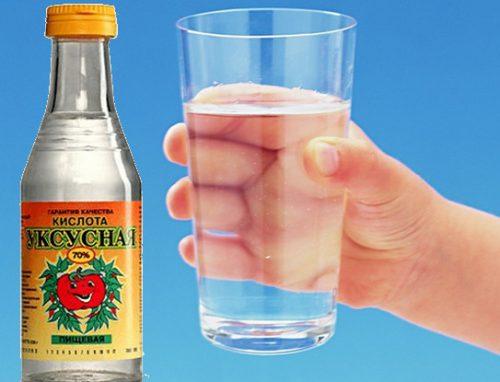 Бутылка уксусной кислоты, рука держит стакан