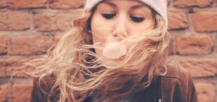 Девушка с развивающимися волосами надувает пузырь из жвачки