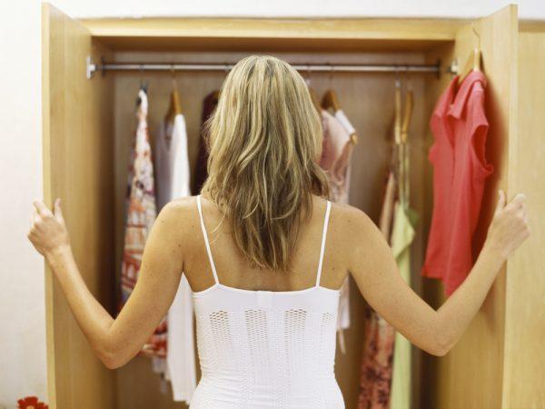 Девушка смотрит в открытый шкаф