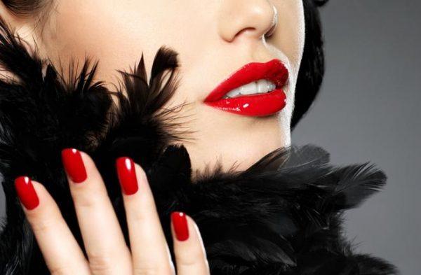 Девушка в чёрном боа из перьев с красным маникюром и красной помадой на губах