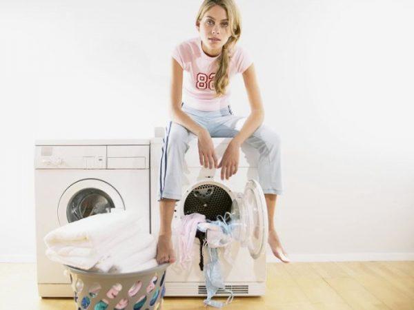 Две стиральные машины и корзина с бельём, девушка сидит на одной