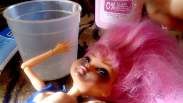 Кукла с пятном от ручки, жидкость для снятия лака и стаканчик
