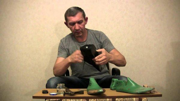 Мужчина держит в руке туфлю, на столе колодки и молоток