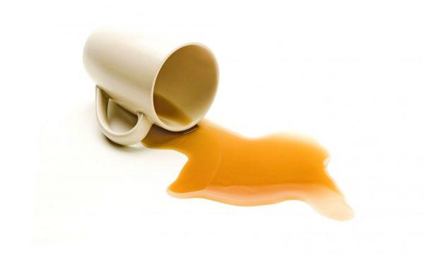Разлитый из белой кружки чай на белой поверхности