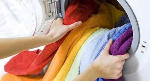 В машинку загружают разноцветные полотенца