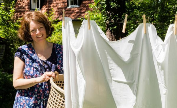 Женщина развешивает бельё