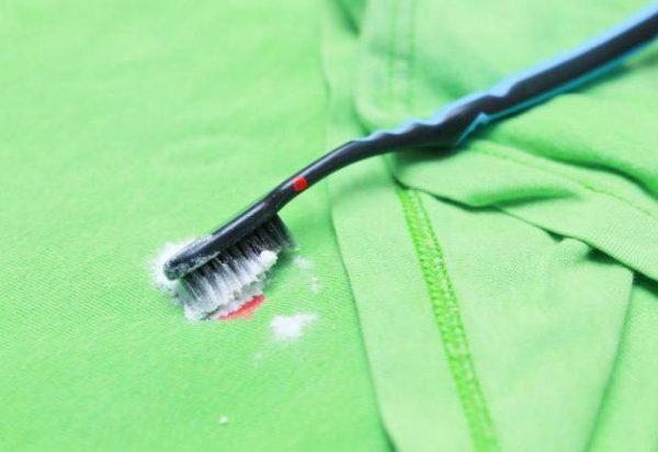 Зубной щёткой оттирают пятно на светло-зелёной вещи