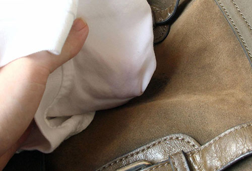 Протирают белой тряпочкой сумку из замши